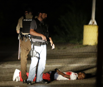 Police stand near a suspect in a parking lot after gunfire during a protest on the anniversary of the death of Michael Brown, Sunday, Aug. 9, 2015, in Ferguson, Mo. St. Louis County Police Chief Jon Belmar said that plainclothes officers had been tracking the man, who they believed was armed, during the protest. Belmar said the man opened fire on police and was struck when the officers returned fire. The man was taken to a hospital, where Belmar said he was in surgery early Monday morning. (AP Photo/Jeff Roberson)