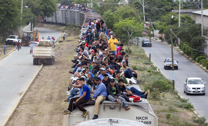 Migrants ride on top of a northern bound train toward the US-Mexico border in Juchitan, southern Mexico, Monday, April 29, 2013. Migrants crossing Mexico to get to the U.S. have increasingly become targets of criminal gangs who kidnap them to obtain ransom money. (AP Photo/Eduardo Verdugo)