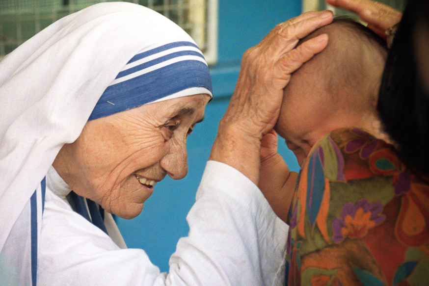 Mother Teresa (L) gives her blessing to a child at the Gift of Love Home on October 20, 1993, in Singapore. The 1979 Nobel Peace Prize winner is on a stop-over while enroute to China where she will set up a fist home for Chinese handicapped children in Shanghai. AFP PHOTO ROSLAN RAHMAN / AFP / ROSLAN RAHMAN